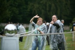 Two people in rainmacs attamepting a team building activity.