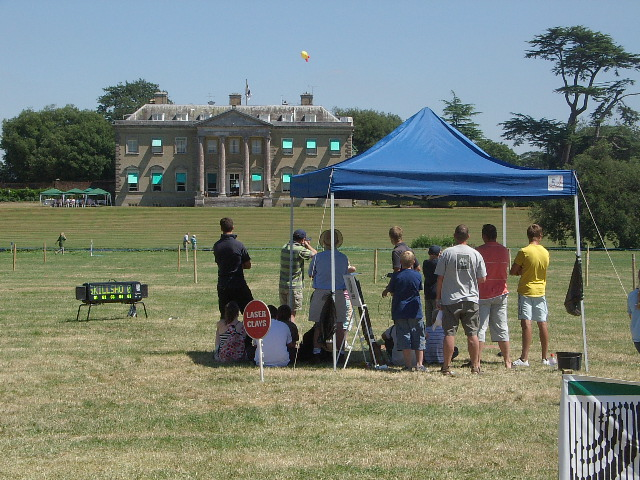 A group taking part in Laser Clay Shooting with a stately home in the background.