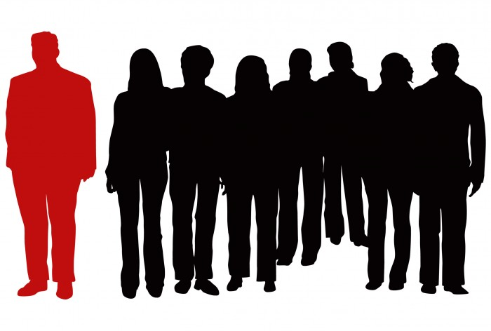 A team of people drawn as shadows with one person set apart and coloured red.